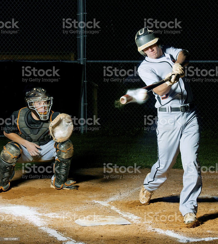 Baseball batter smashes ball, it's headed for the fenses! stock photo