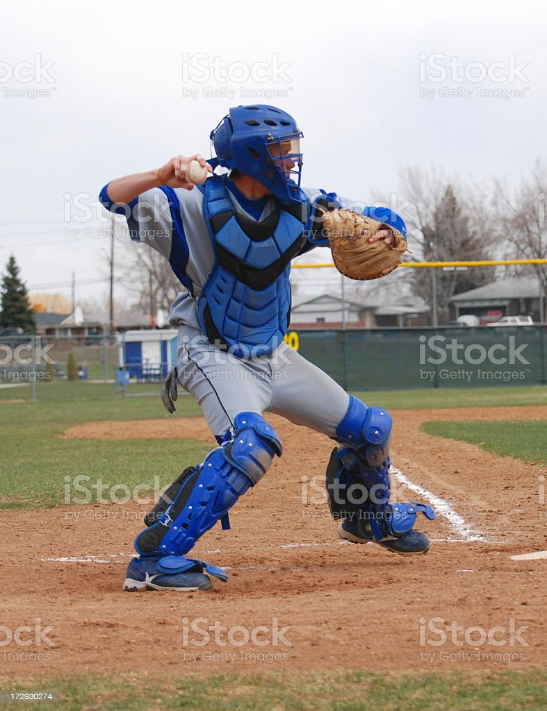 A baseball catcher gets ready to throw the ball.