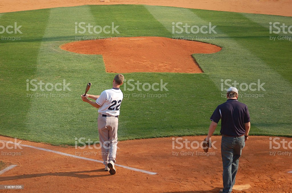 A baseball coach hits practice balls to his players.