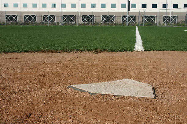 baseball field home plate and fould line leading towards first base wiith building in backround infield stock pictures, royalty-free photos & images