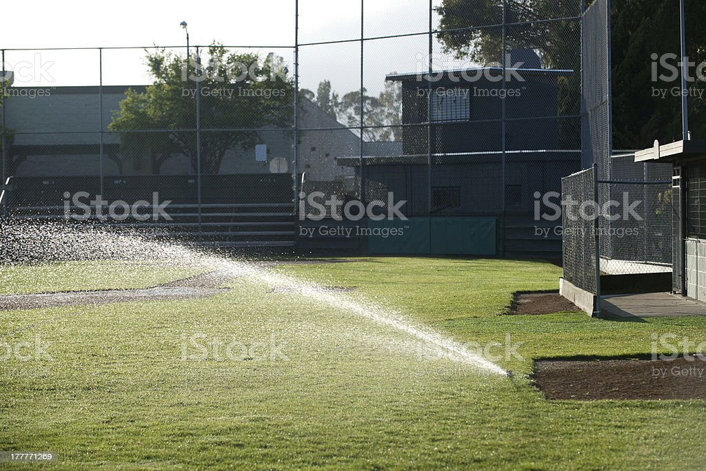 Baseball field sprinkler waters the grass, pointed left royalty-free stock photo