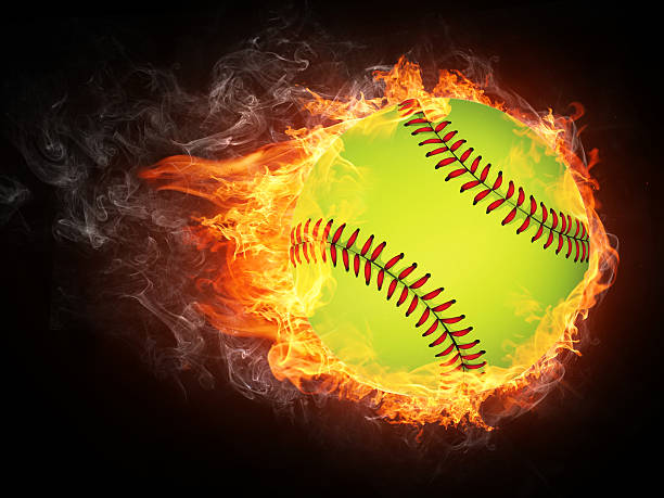 baseball flies through black background engulfed in flames - softball stock photos and pictures