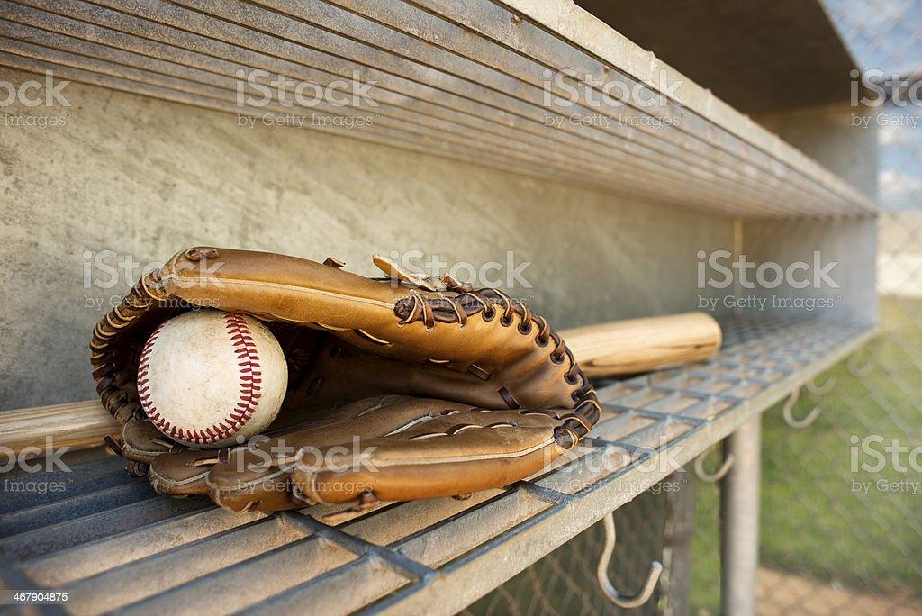 Baseball, glove and bat in dugout stock photo