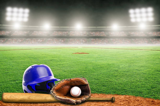 Baseball Helmet, Bat, Glove and Ball on Field in Outdoor Stadium With Copy Space Blue baseball helmet, bat, glove and ball on field at brightly lit outdoor stadium. Focus on foreground and shallow depth of field on background and copy space. Fictitious stadium created in Photoshop. baseball diamond stock pictures, royalty-free photos & images