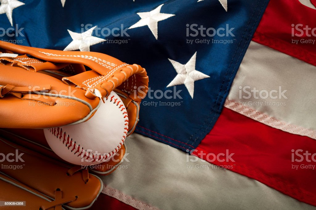 Baseball in a leather glove on US flag stock photo