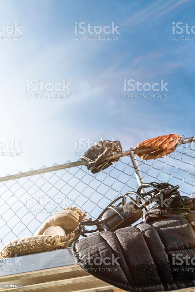 Baseball in catcher's mitt with other catcher's gear on bench stock photo