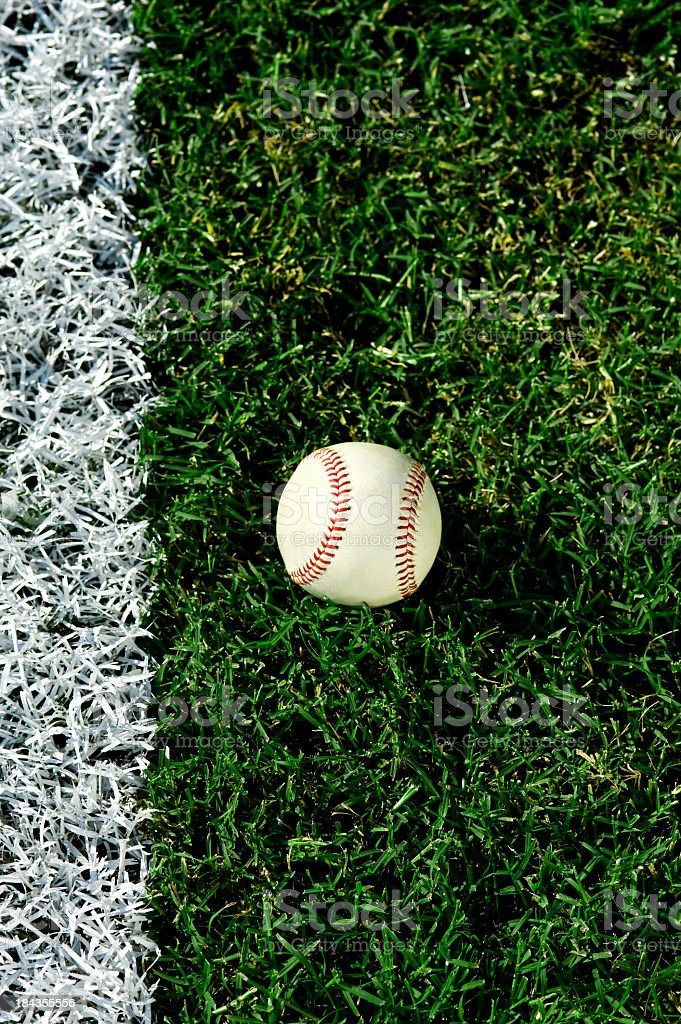 Baseball in front of foul line on grass stock photo