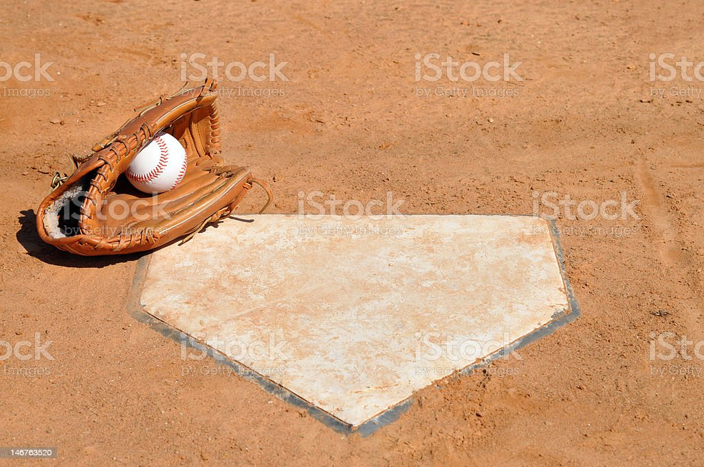Baseball in Glove at Home Plate stock photo