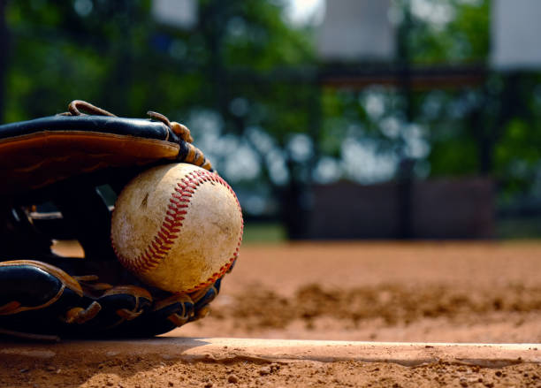 Baseball in glove on team field. Baseball in glove laying on pitcher's mound of ball field.  Old used sports equipment for team sport. baseball sport stock pictures, royalty-free photos & images