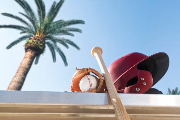 baseball in glove with bat and batting helmet on bench - spring training - spring training stock photos and pictures