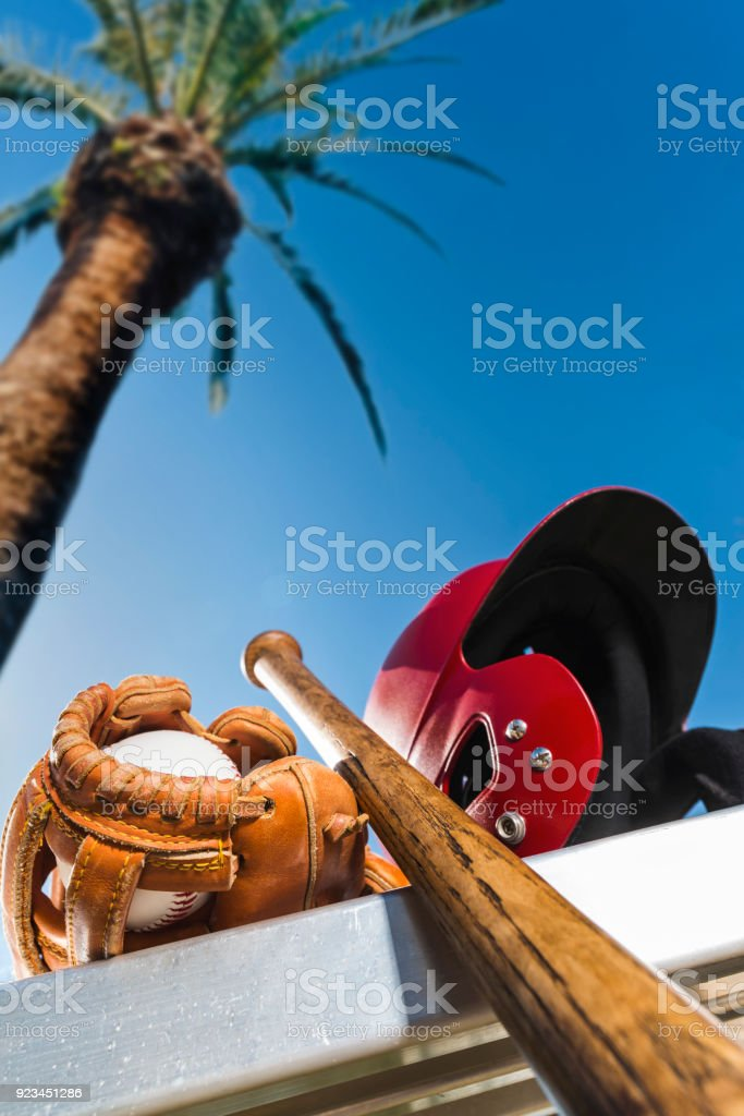 Baseball in glove with bat and batting helmet on bench - Spring Training stock photo