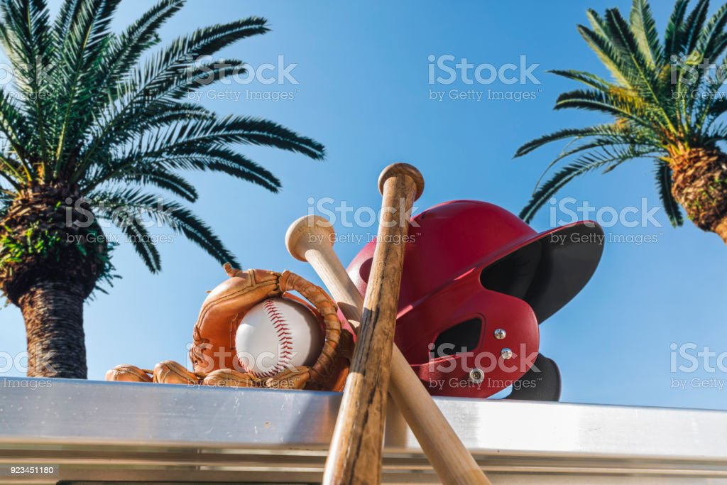 Baseball in glove with bats and batting helmet on bench - Spring Training stock photo