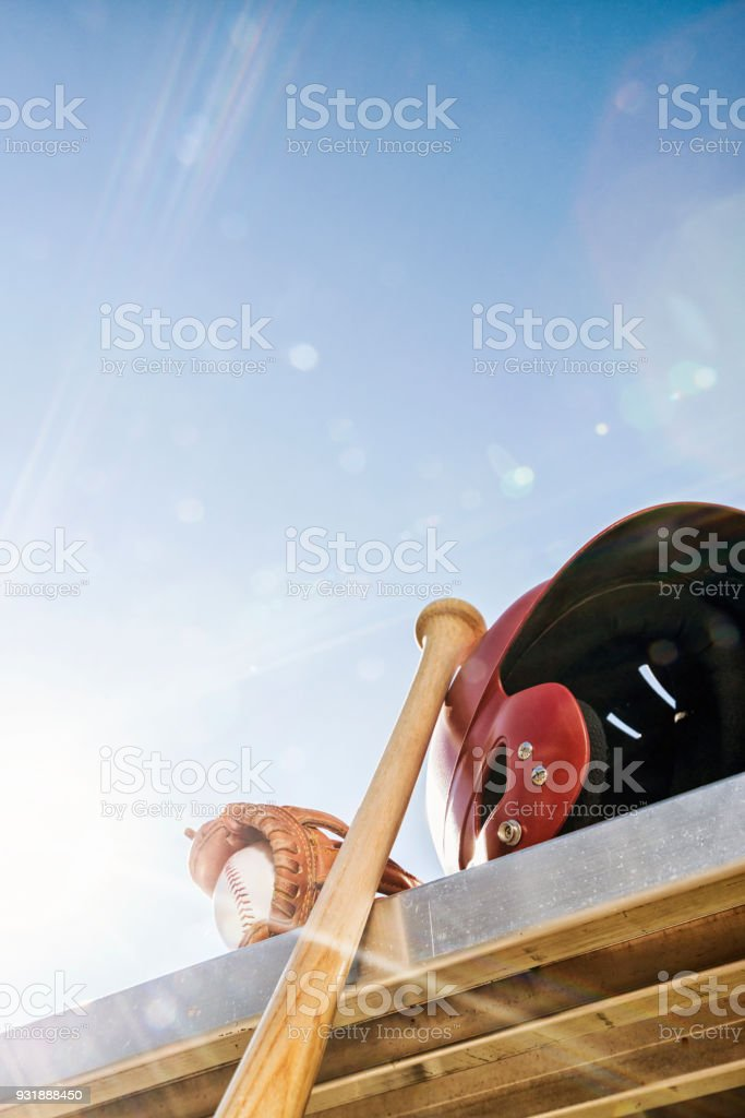 Baseball in glove with wooden bat and batting helmet on bench - Lens Flare stock photo