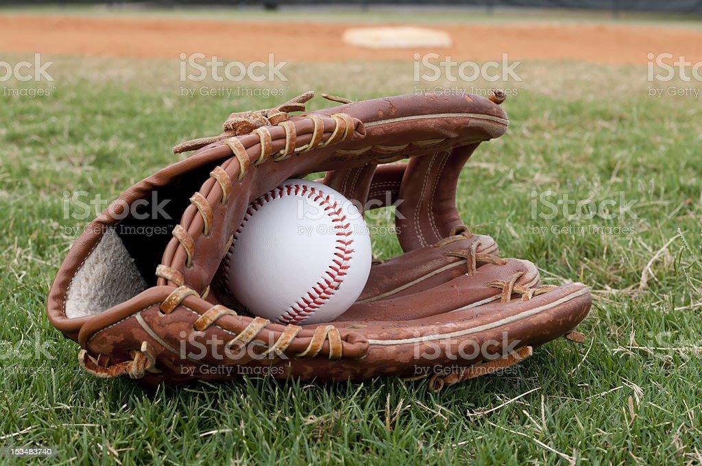 Baseball in Old Glove on Field stock photo