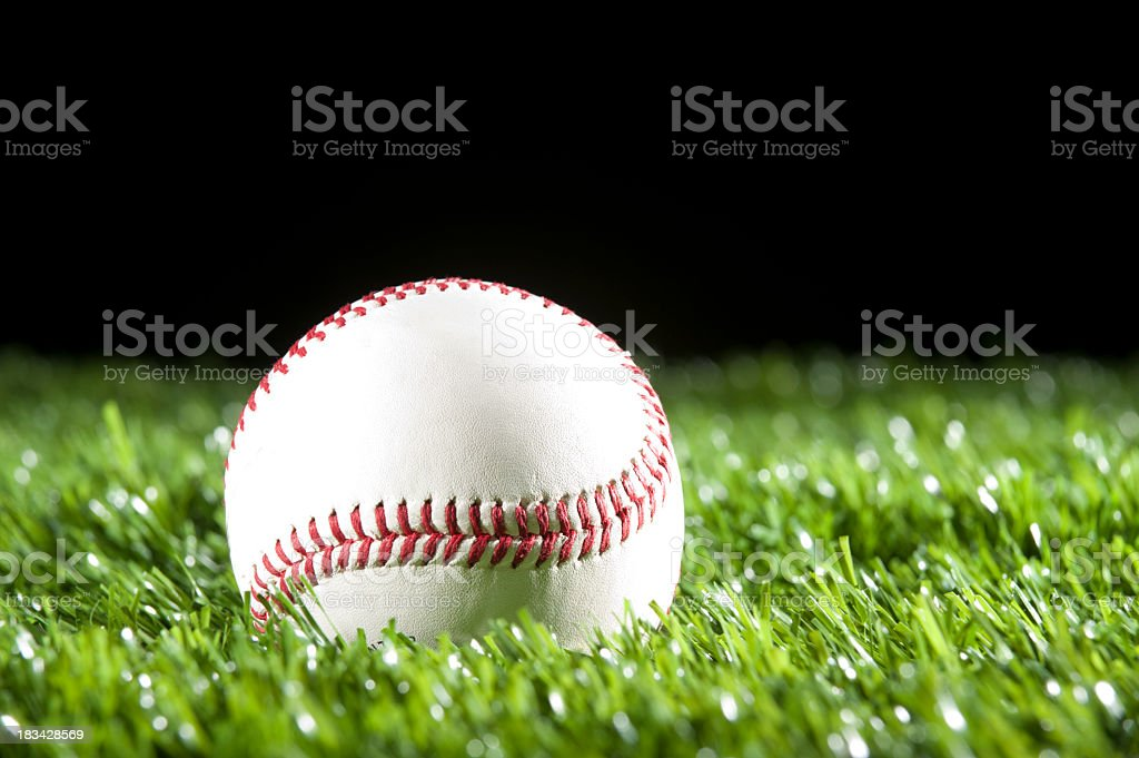 Baseball in the grass at night stock photo