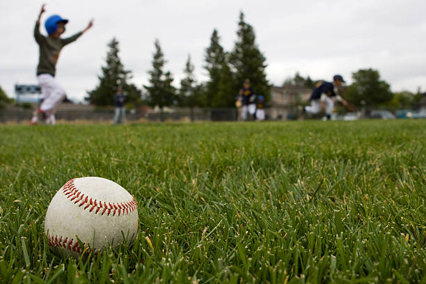 Baseball in the Grass TBall game in progress with stray ball on the grass all star stock pictures, royalty-free photos & images