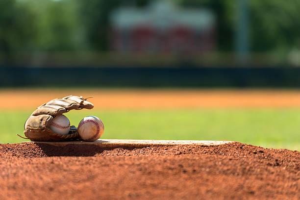 Baseball mitt and baseballs on pitchers mound stock photo