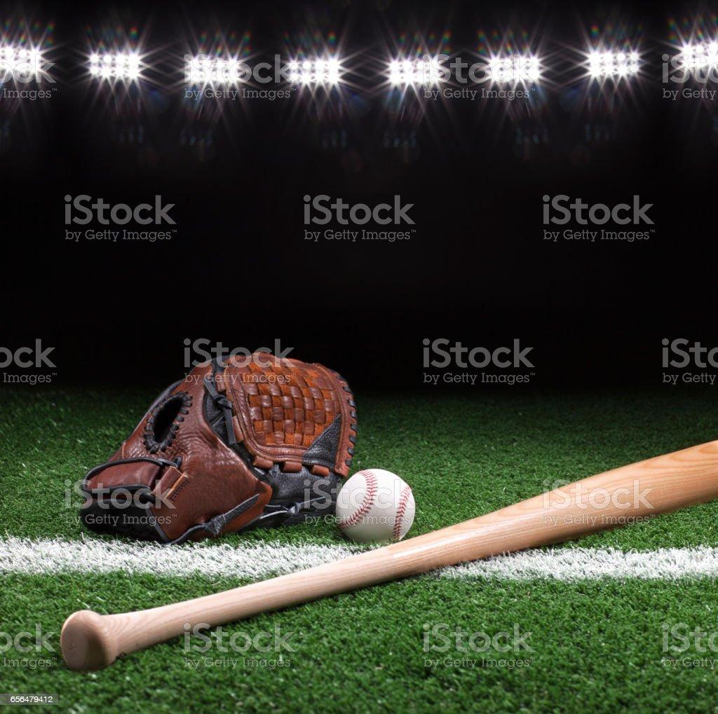 Baseball mitt ball and bat at night under stadium lights stock photo