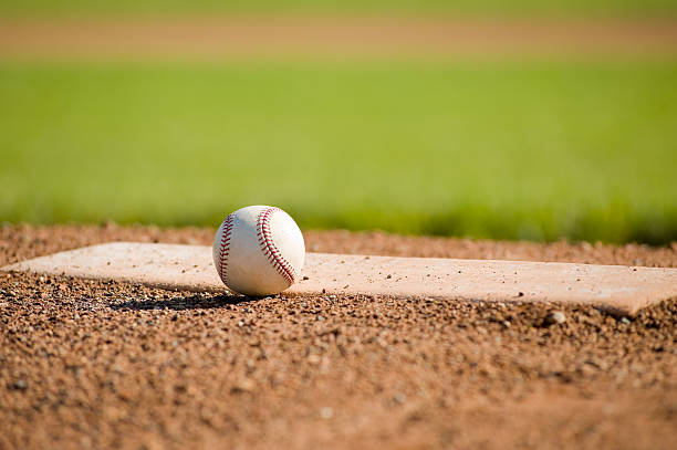Baseball on a mound with the field in the background A baseball on the pitcher's mound or plate, with copy space baseball diamond stock pictures, royalty-free photos & images