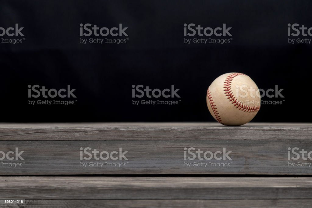 Baseball on a old rustic wooden desk with copy space black background stock photo