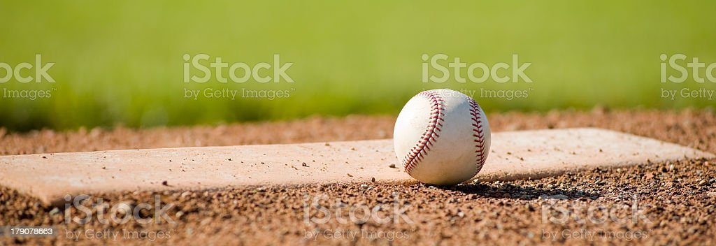 a leather baseball lying next to the pitching rubber on a pitching...