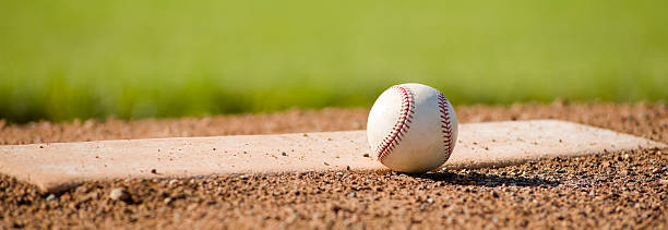 A baseball on a white mound on a field stock photo