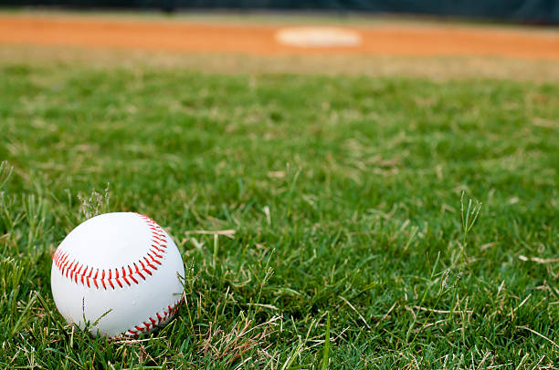 Baseball on Field Baseball on field with base and outfield in background. baseball diamond stock pictures, royalty-free photos & images