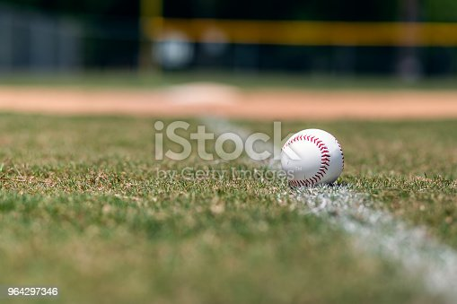 Baseball on foul line with base and outfield out of focus in background.