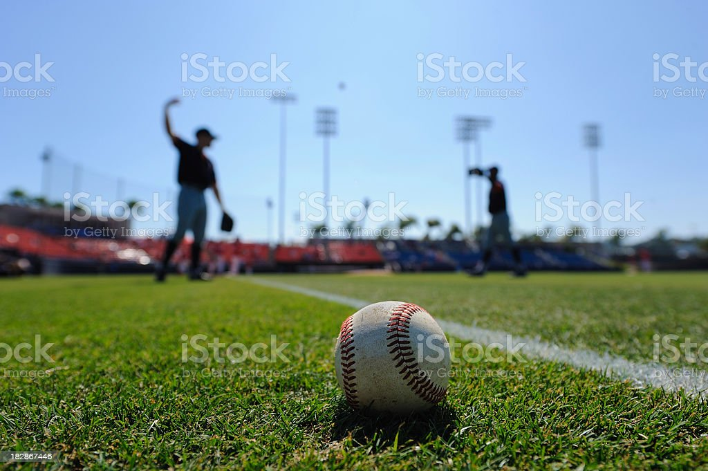 Baseball on the field with players in the background stock photo