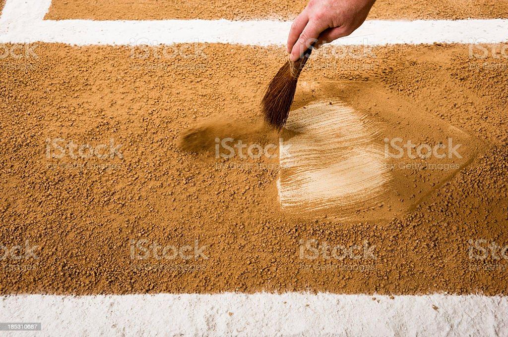 Baseball or softball umpire cleaning home plate. Play Ball!!! stock photo