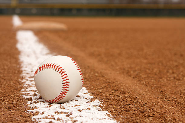 Baseball over chalk line of stadium field Baseball on the Infield Chalk Line with Third Base beyond baseball diamond stock pictures, royalty-free photos & images