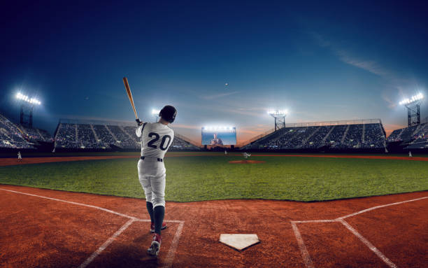 Baseball Baseball player at professional baseball stadium in evening during a game. baseball sport stock pictures, royalty-free photos & images