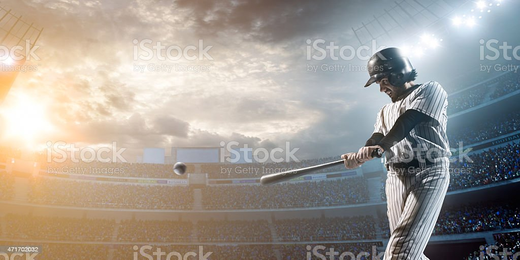 Baseball player hitting a ball in stadium stock photo