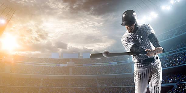 Baseball player hitting a ball in stadium stock photo