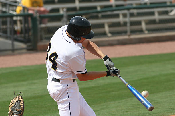 Baseball player hitting a ball with his bat on the field stock photo