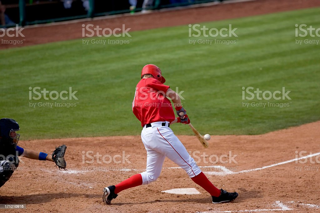 Baseball player hitting ball during a game stock photo