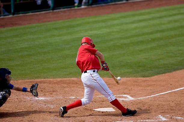 Baseball player hitting ball during a game stock photo