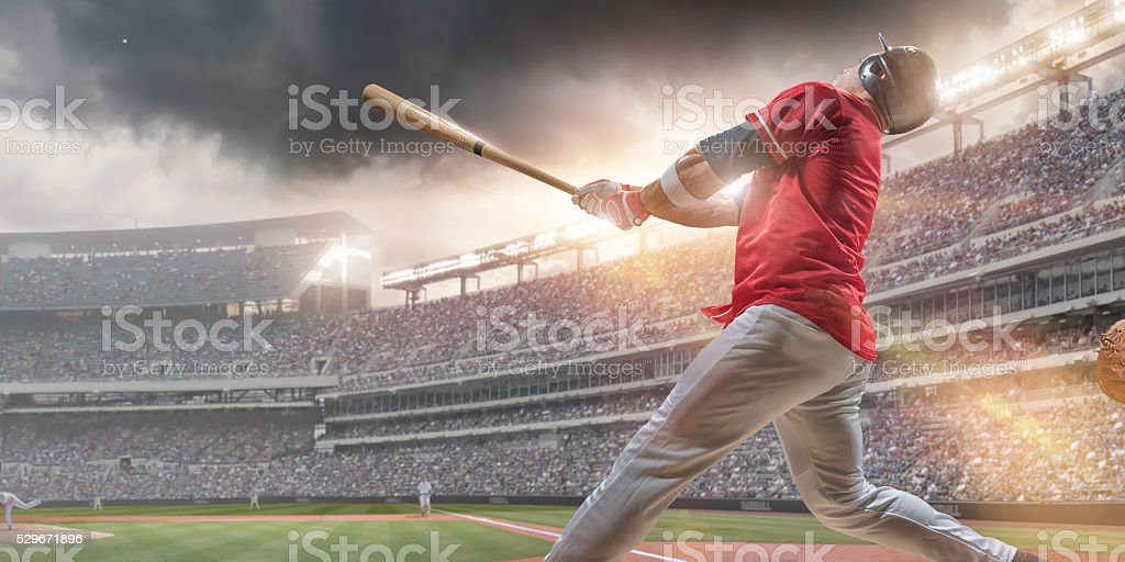 Baseball Player Hitting Ball During Baseball Game In Outdoor Stadium stock photo