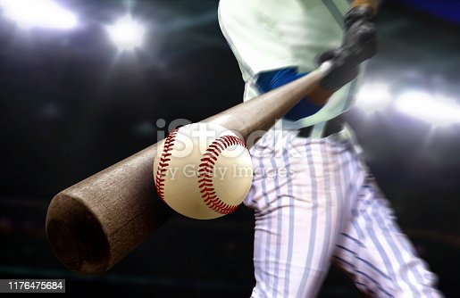 Baseball player swing hitting ball with bat in close up under stadium spotlights