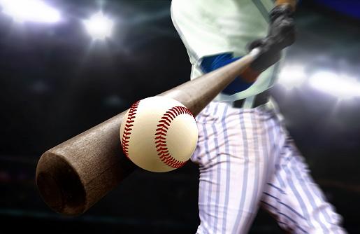 Baseball player hitting ball with bat in close up under stadium spotlights