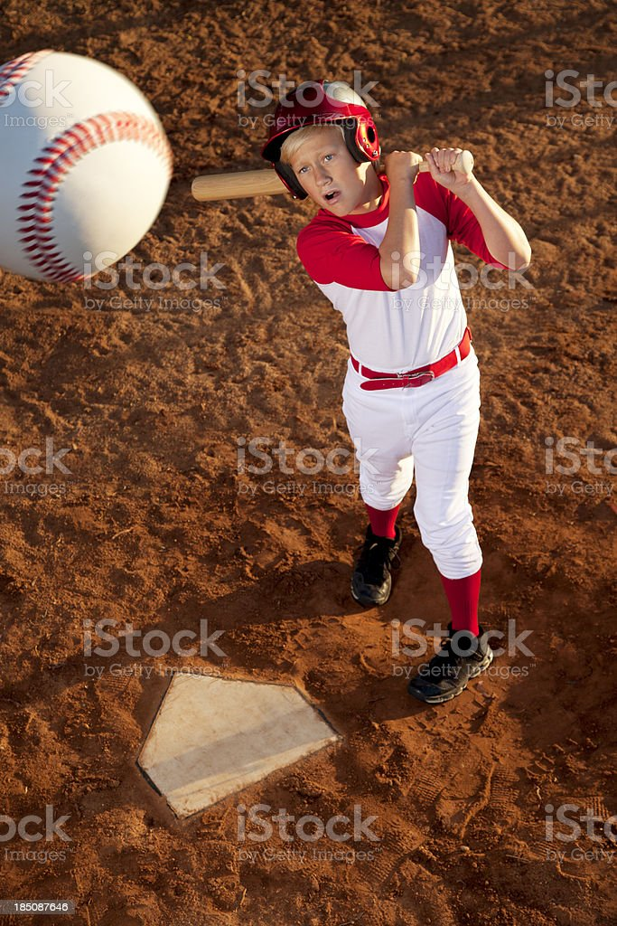 This is a photo a 12 year old boy hitting a baseball up in the air....