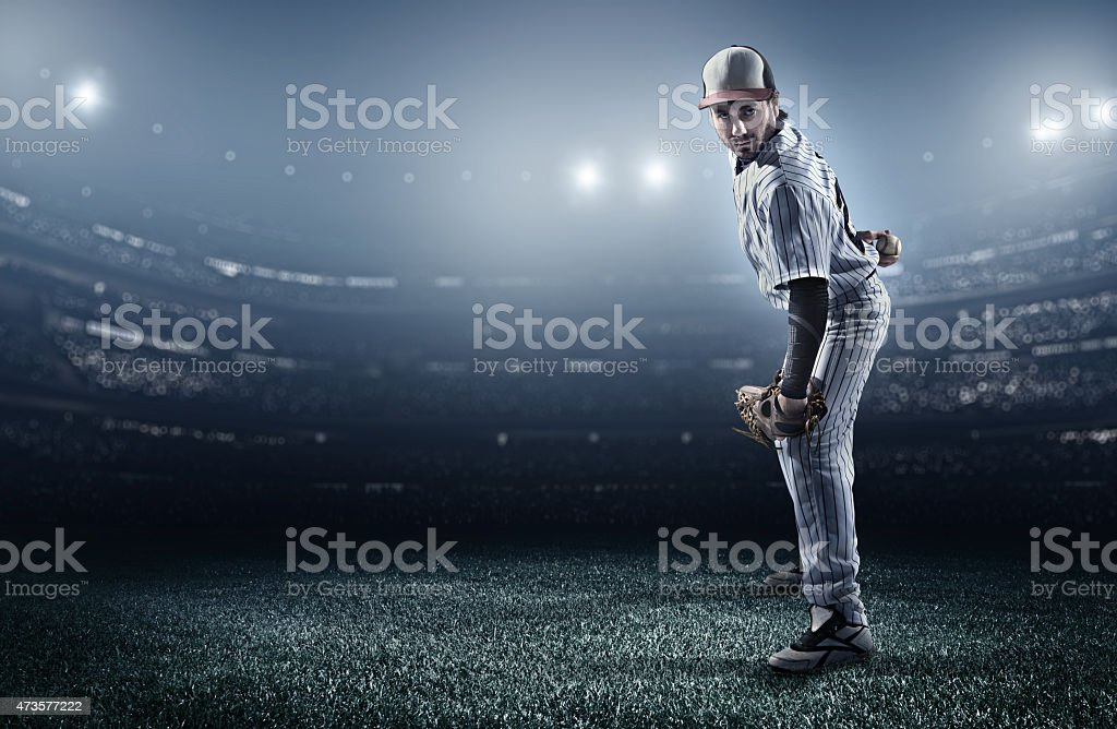 A baseball player in a stadium about to make a pitch  stock photo