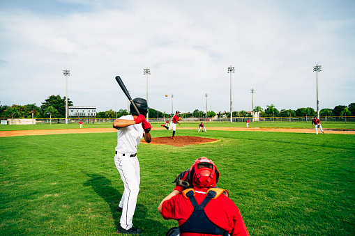 Baseball player in batter's box watching thrown pitch