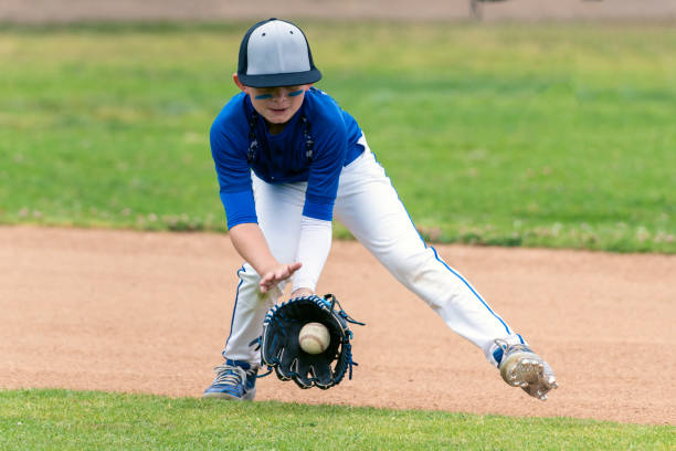 Baseball player leaving it all out on the field. Youth baseball player in blue uniform fielding a ground ball into his glove in the infield during a game. infield stock pictures, royalty-free photos & images