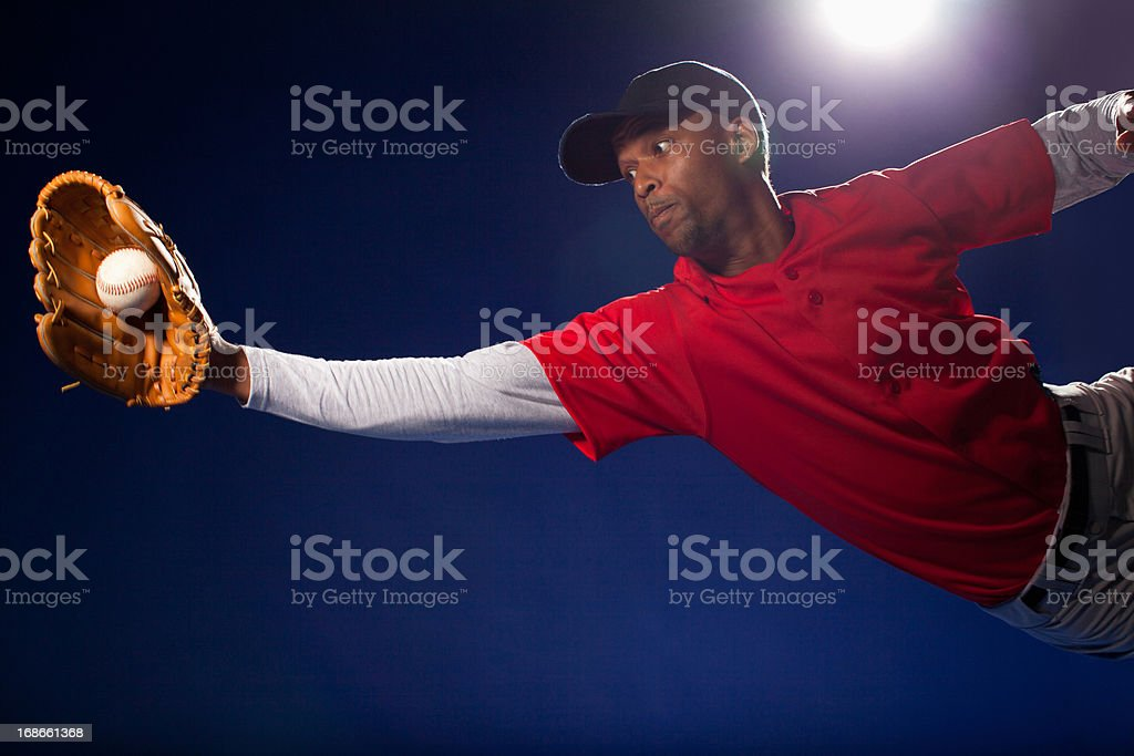 Baseball player lunging for ball stock photo