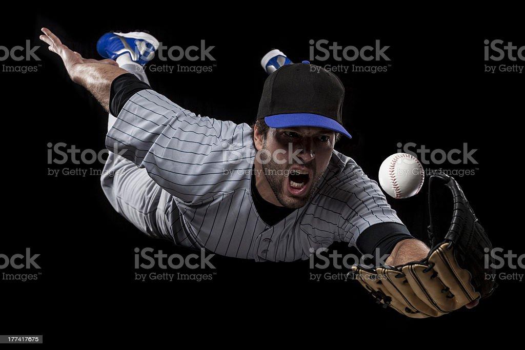 Baseball Player on a blue uniform, catching a ball on a black...