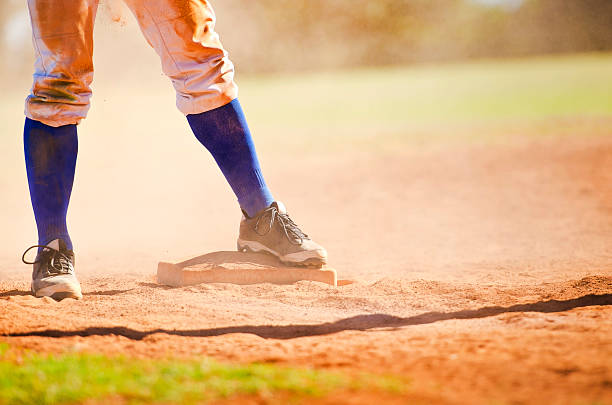 Baseball player on the base Baseball player wearing blue socks standing on a baseball base. studded stock pictures, royalty-free photos & images