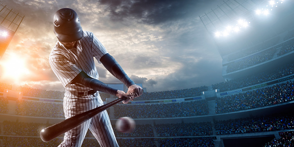 Baseball player about to strike ball during baseball game on outdoor stadium under dramatic stormy skies.