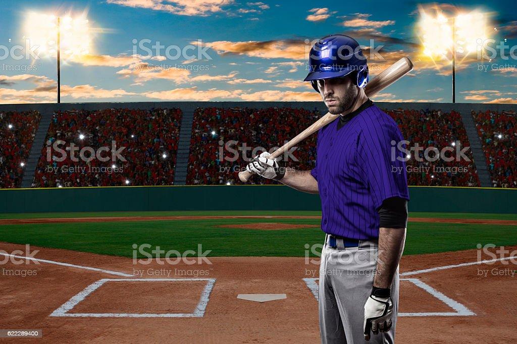 Baseball Player with a blue uniform on baseball Stadium.