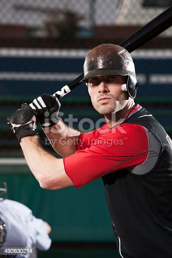 Waist up portrait of Caucasian baseball player in helmet with bat, ready to hit the ball. Copy space on bottom. CLICK FOR SIMILAR IMAGES AND LIGHTBOXES WITH FITNESS/OUTDOOR IMAGES OR MEN. http://www.quavondo.com/thumbs/IStockLightboxFitness.jpg